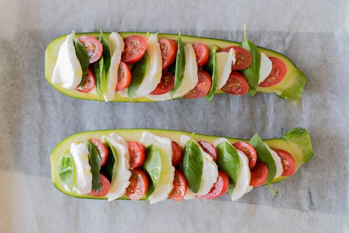 Gevulde courgettes uit de oven. Zo maak je gevulde courgette caprese met pesto, tomaat, mozzarella en verse basilicum. #courgette #saladecaprese #italiaans | Anniepannie.nl