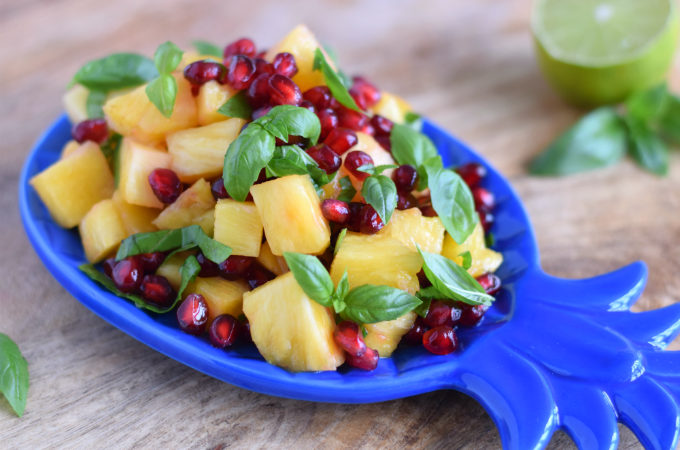 Fruitsalade met ananas, granaatappel en basilicum